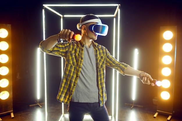 Homme jouant dans un casque de réalité virtuelle et une manette de jeu dans un cube lumineux. intérieur sombre du club de jeu, projecteur sur l'arrière-plan, technologie vr avec vision 3d