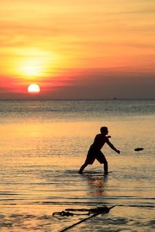 Homme jouant disque volant plage contre beau ciel coucher de soleil