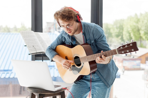 Homme jouant de la guitare acoustique dans la maison
