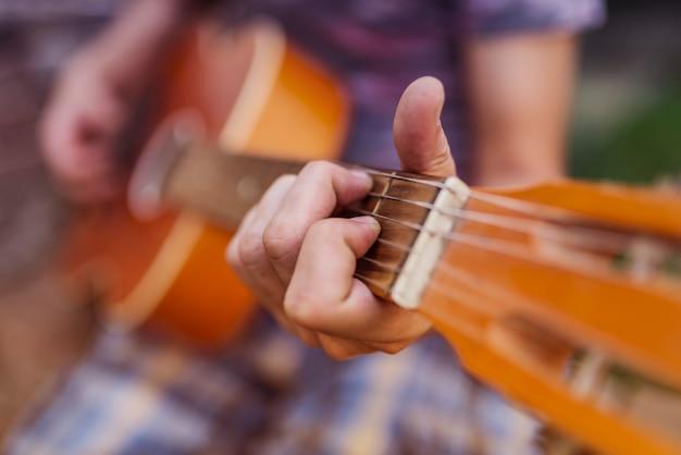 Homme jouant de la guitare acoustique à l'extérieur