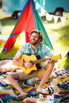 Homme jouant de la guitare au camping