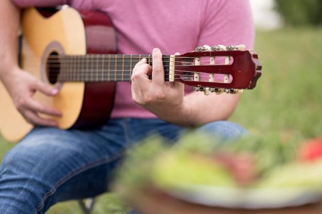 Homme jouant de la guitare à l'extérieur à côté du barbecue