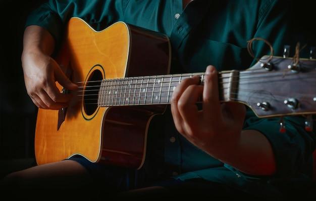 Homme jouant de la guitare sur fond noir