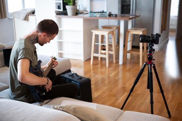 Homme jouant de la guitare à la maison