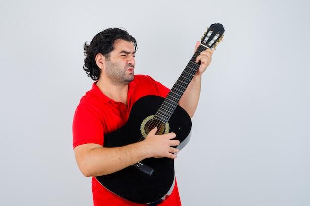 Homme jouant de la guitare en t-shirt rouge et à la recherche concentrée