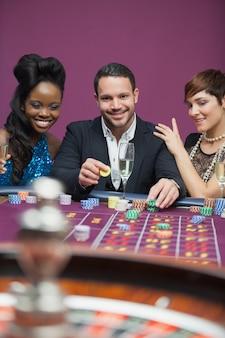 Homme jouant à la roulette avec des femmes de remorquage de chaque côté du casino