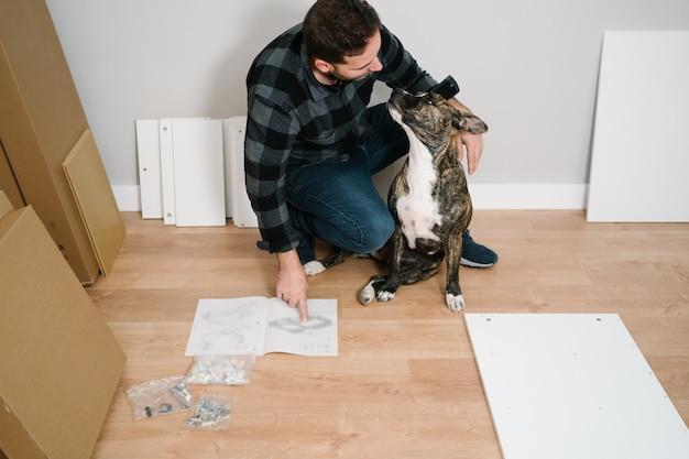 Homme jouant avec son chien pendant qu'il assemble lui-même un meuble. fais le toi-même