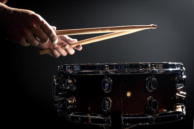 Un homme joue avec des bâtons sur un tambour, un batteur joue d'un instrument à percussion, copiez l'espace.