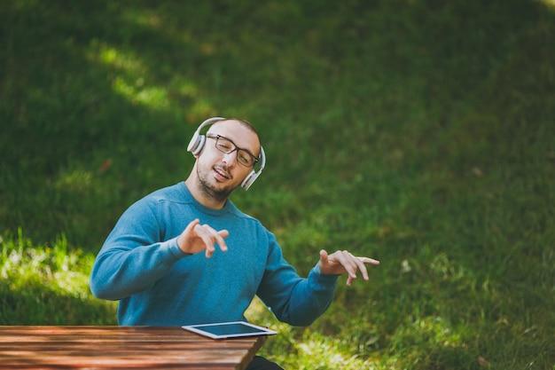 L'homme joue avec les doigts en l'air comme du piano. étudiant dans des lunettes de chemise bleue décontractée assis à table avec des écouteurs, tablette dans le parc de la ville, écouter de la musique, se reposer à l'extérieur sur la nature. concept de loisirs de style de vie.