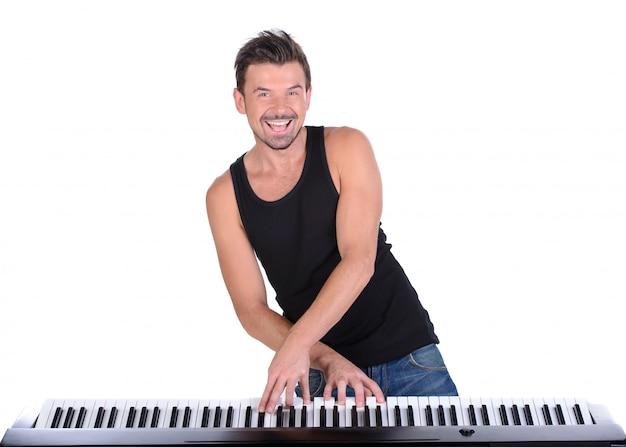 L'homme joue du piano numérique et sourit.
