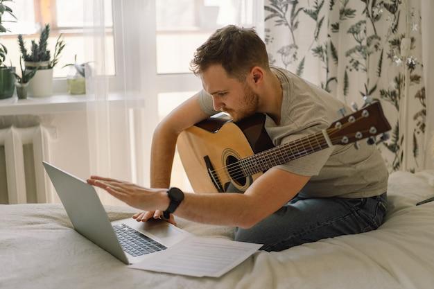 L'homme joue de la guitare acoustique dans une leçon en ligne