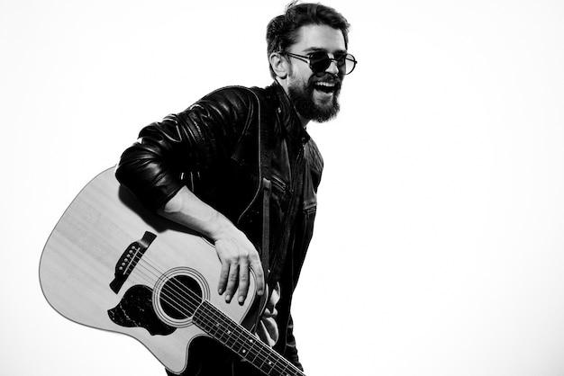 Un homme joue de la guitare dans une veste en cuir noir avec des lunettes de soleil sur un fond clair.