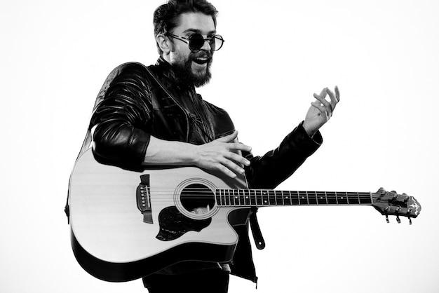 Un homme joue de la guitare dans une veste en cuir noir avec des lunettes de soleil sur un fond clair