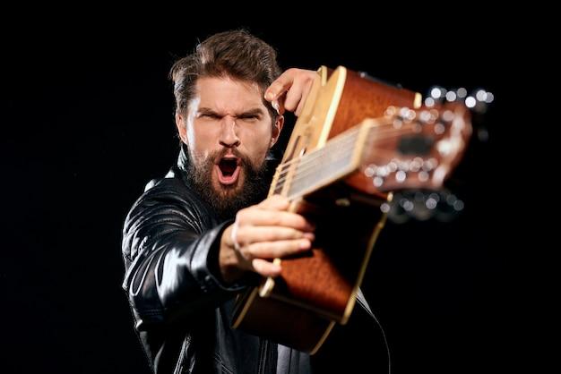 Un homme joue de la guitare, une rock star, un musicien élégant avec une guitare