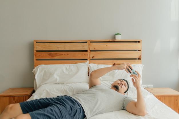 L'homme joue à un jeu mobile avec son smartphone sur le lit.