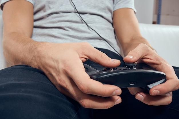 Un homme joue à un jeu d'ordinateur dans des consoles avec des manettes dans des écouteurs avec un ordinateur portable à la maison sur le canapé