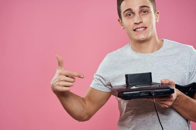Un homme joue à un jeu d'ordinateur dans des consoles avec des manettes dans des écouteurs avec un ordinateur portable