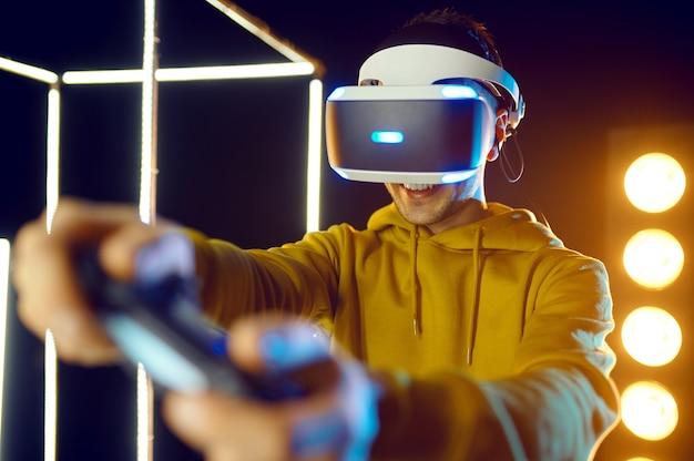 L'homme joue le jeu en utilisant un casque de réalité virtuelle et une manette de jeu en cube lumineux, vue de face