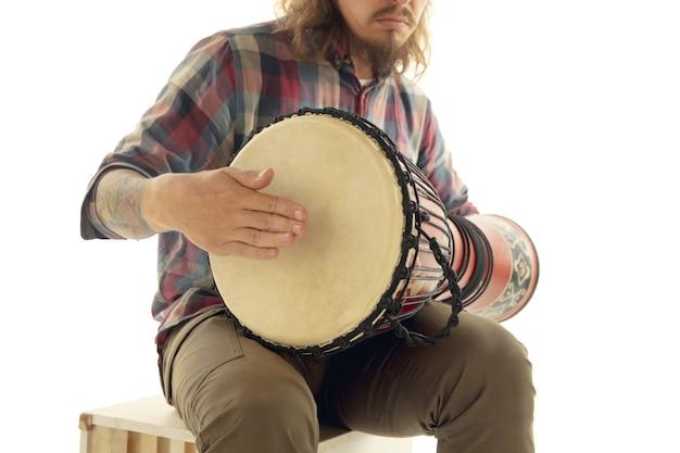 L'homme joue des percussions de darbouka à tambour ethnique, gros plan musicien isolé sur fond de studio blanc. mains masculines tapant djembé, bongo en rythme. instruments de musique faits à la main, son de la culture mondiale.