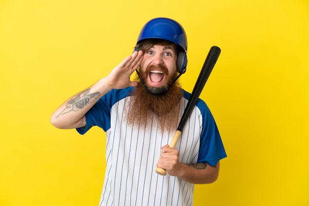 Homme de joueur de baseball rousse avec casque et batte isolé sur fond jaune criant avec la bouche grande ouverte
