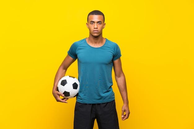 Homme de joueur de football afro-américain sur jaune isolé