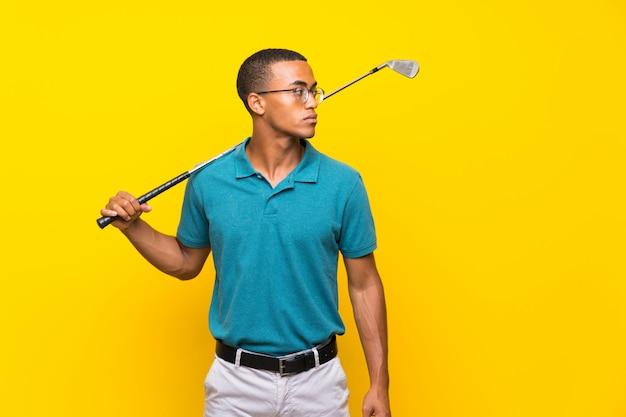 Homme de joueur de golfeur afro-américain sur jaune isolé