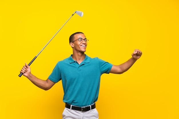 Homme de joueur de golfeur afro-américain sur mur jaune isolé