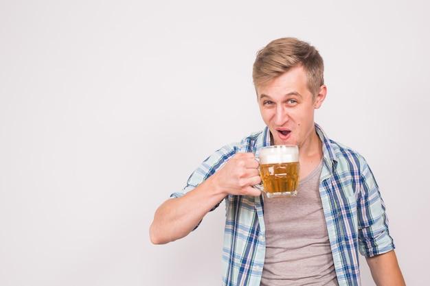 Homme joyeux avec une barbe avec une chope de bière sur un mur bleu, de l'alcool