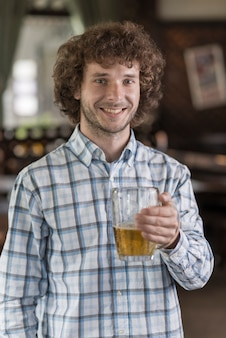 Homme joyeux avec de la bière au bar