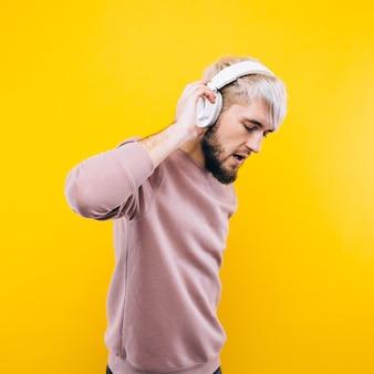 Homme joyeux écoutant de la musique sur des écouteurs sur fond jaune