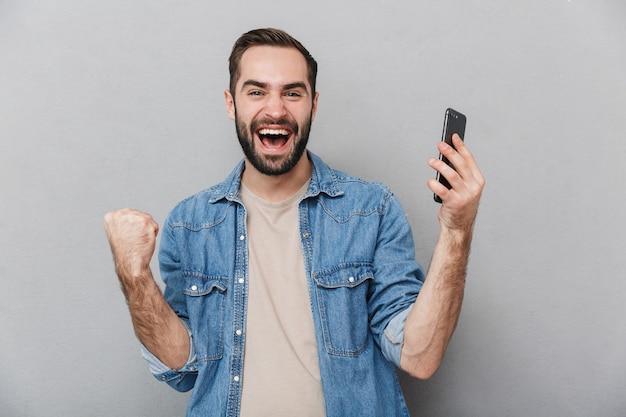 Homme joyeux excité portant chemise isolé sur mur gris, à l'aide de téléphone mobile, célébrant