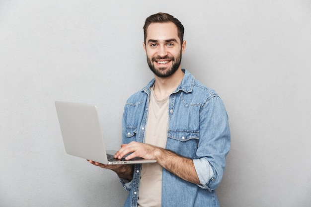 Homme joyeux excité portant chemise isolé sur mur gris, montrant un ordinateur portable