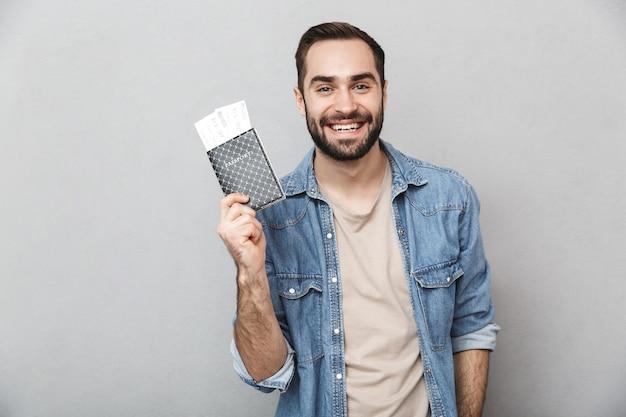 Homme joyeux excité portant chemise isolé sur mur gris, tenant un passeport avec des billets d'avion