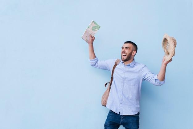 Homme joyeux jeune voyageur riant et debout sur fond bleu