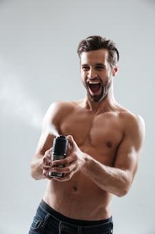 Homme joyeux jouant avec déodorant