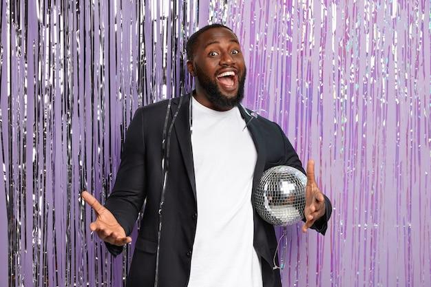 Un homme joyeux à la peau sombre profite de la musique de soirée dansante qui tient une boule disco brillante, vêtu d'un costume noir élégant, a de bons week-ends, se réjouit de la célébration