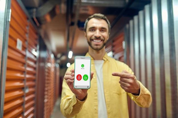 Homme joyeux pointant du doigt sur l'écran du smartphone