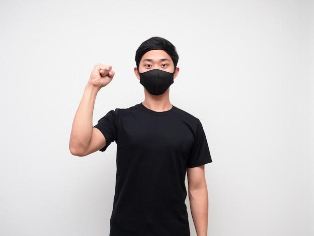 Un homme joyeux portant un masque de protection montre un poing sur fond blanc