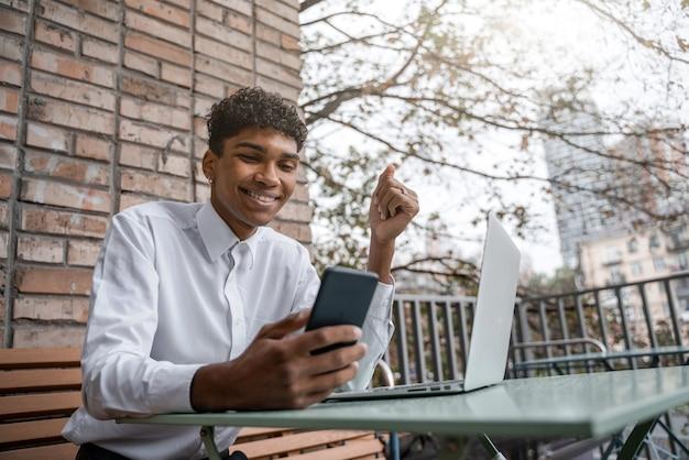 Un homme joyeux travaille sur un ordinateur portable et sourit à l'aide d'un smartphone. un gay noir est assis sur une terrasse d'été ou une véranda près d'un café. vue du centre-ville d'affaires de printemps