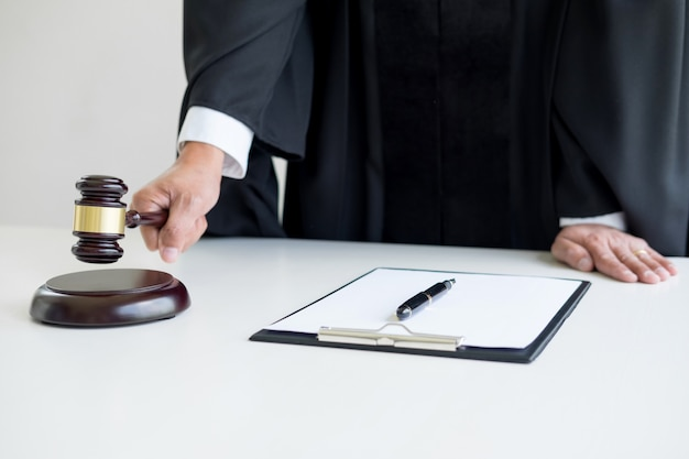 Homme juge avocat dans une salle d'audience striking the gavel sur le bloc de sonde