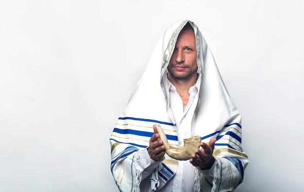 Homme juif enveloppé dans un talit, châle de prière tenant le shofar (corne). concept de roch hachana (nouvel an juif), shabbat et yom kippour. un rabbin donnant un shofar à la main, avant les vacances de tishrei