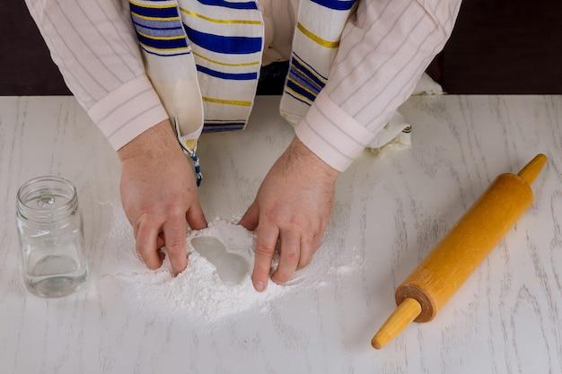 Un homme juif orthodoxe prépare une matsa casher plat à la main pour la cuisson