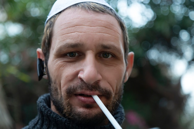 Homme juif portant des écouteurs bluetooth kippa et fumant une cigarette