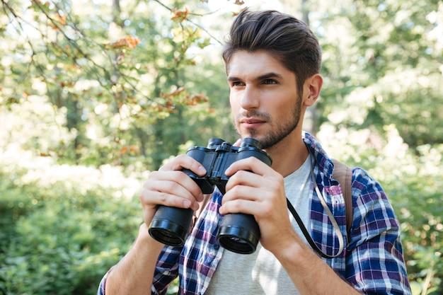 Homme avec des jumelles en forêt