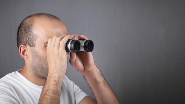 Homme avec des jumelles regardant au loin.