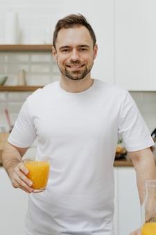Homme avec un jus d'orange à la main