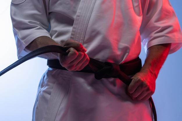 Homme en kimono blanc et ceinture noire karaté d'entraînement sur fond gris.