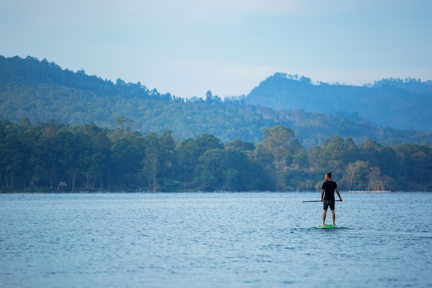 Un homme sur le lac monte une planche de sup.