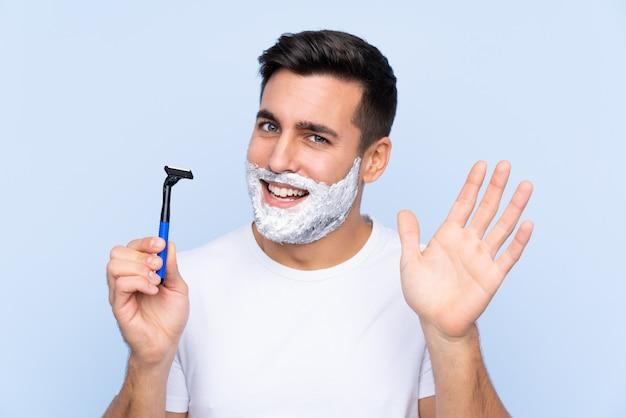 Homme avec lame de rasoir sur mur bleu isolé