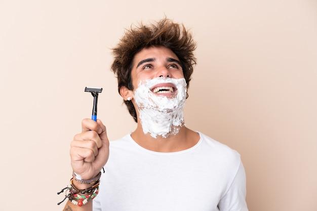 Homme avec lame de rasoir sur mur isolé